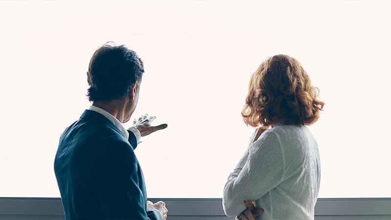 A man talking to woman pointing his hard to a horizon